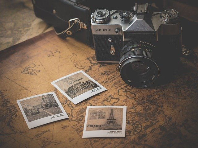 A sepia toned map with a few sepia polaroids spread out over it and an old camera sat next to it.