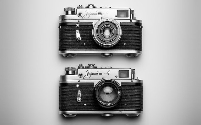 Two vintage cameras. One on top of the other. You could use cameras like this to create images which you could then upload to Wikimedia commons using the Attribution-Share Alike License. From Wikimedia commons your images could appear on many different language versions of Wikipedia.