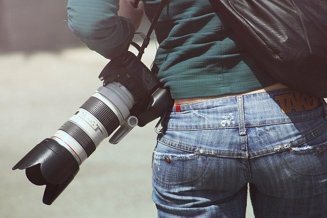 A rear view shot of a photographer carrying a camera with a long telephoto lens.